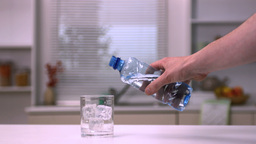 Hand pouring water into a glass Stock Video Footage