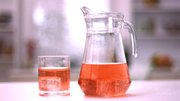 Ice cubes spinning in a glass and in a jug with ju Footage