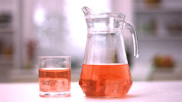 Ice cubes spinning in a glass and in a jug with ju Stock Video Footage