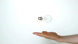 Mans hand throwing transparent light bulb Live Action