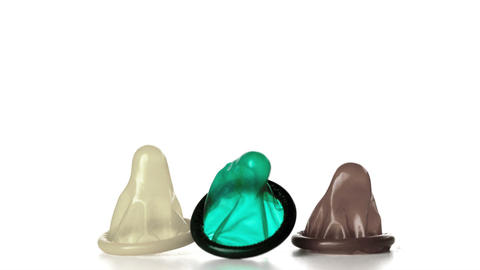 Three condoms falling on white background Footage