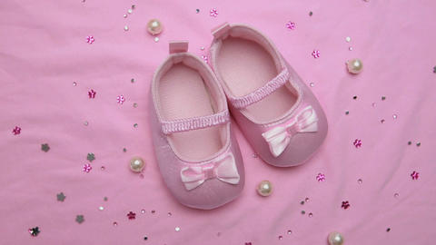 Pink baby booties on pink blanket with pearls Footage
