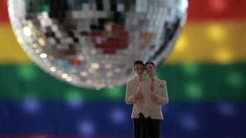 Gay groom cake toppers in front of rainbow flag Stock Video Footage