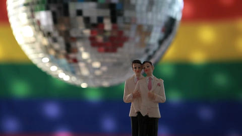 Gay groom cake toppers in front of rainbow flag Footage