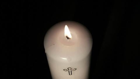 Candle with cross embellishment burning and being  Footage