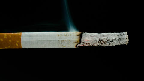 Burning Cigarette On Black Background In Reverse stock footage