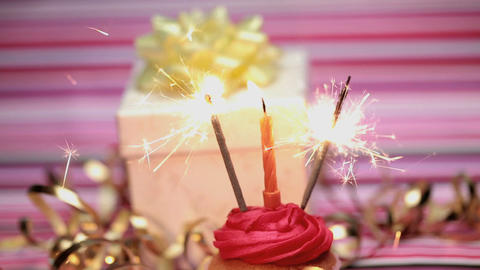 Sparklers on a birthday cupcake with gift Footage