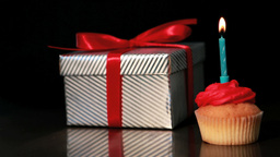 Candle on cupcake blown beside gift Footage