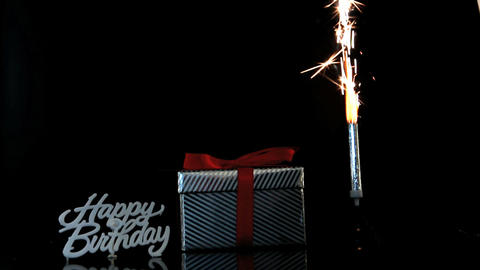 Sparkler burning beside gift and happy birthday sign Live Action