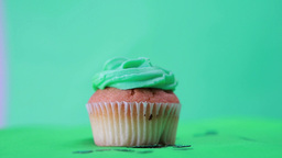 St patricks day cupcake spinning around with shamrock confetti falling Live Action