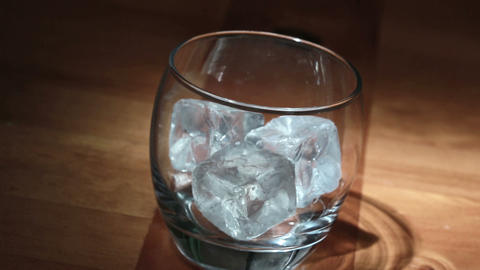 Hand putting ice into tumbler then pouring whiskey Footage