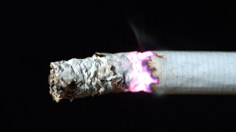 Cigarette burning on black background close up Footage