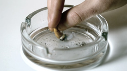 Hand extinguishing cigarette in empty ashtray Live Action