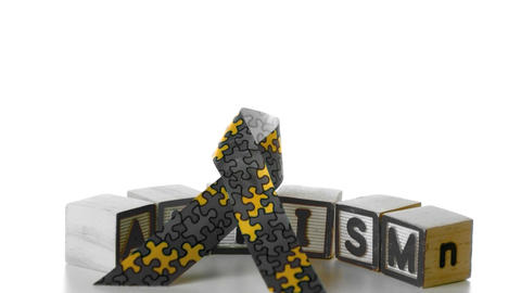 Awareness ribbon falling onto blocks spelling auti Footage