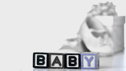 Baby blocks falling over beside booties and gift box Stock Video Footage