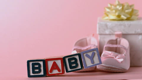 Baby blocks toppling over with booties and gift bo Footage