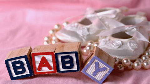 Baby in letter blocks beside booties and pearls on Footage
