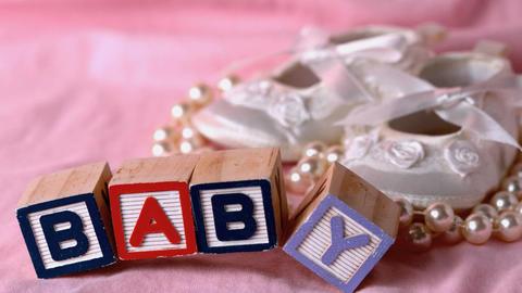 Baby in letter blocks beside booties and pearls on pink blanket Footage