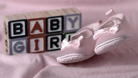 Baby booties falling on pink blanket with baby gir Stock Video Footage
