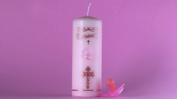 Pink pacifier falling beside baptism candle on pink background Footage
