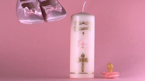 Baby shoes falling beside baptism candle and pacif Stock Video Footage