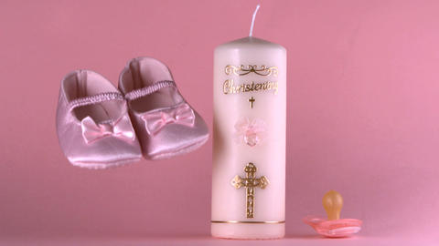 Baby shoes falling beside baptism candle and pacif Footage
