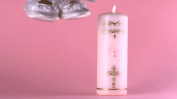 Baby shoes falling beside lit baptism candle on pi Stock Video Footage