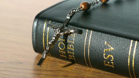 Rosary beads falling onto bible on a table Footage