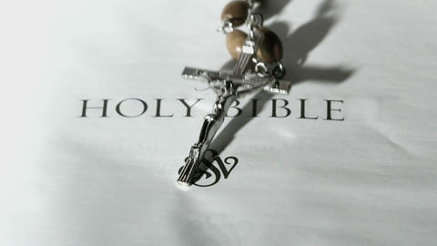 Rosary beads falling onto first page of holy bible Footage