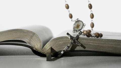 Rosary beads falling onto open bible on white back Footage