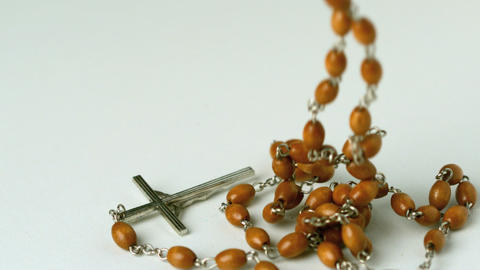 Rosary beads falling on white surface Footage
