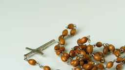 Rosary beads falling on white surface Stock Video Footage