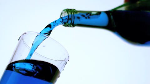 Blue liquid pouring into glass low angle close up Stock Video Footage