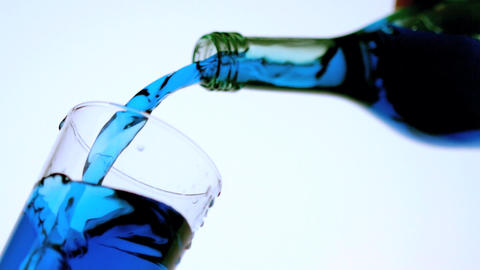 Blue liquid pouring into glass low angle close up Footage