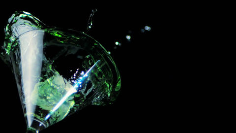 Ice falling into cocktail glass of green liquid Stock Video Footage