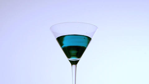 Ice falling into cocktail glass of blue liquid on Stock Video Footage