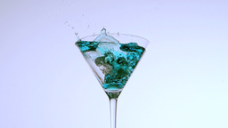 Ice falling into cocktail glass of blue liquid on  Footage