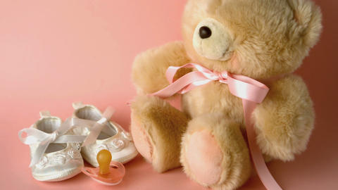 Pink soother falling in front of baby shoes and a Stock Video Footage