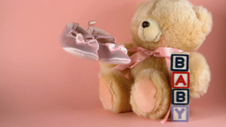 Baby shoes falling next to a teddy bear and baby b Footage