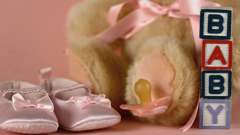 Pink soother falling besides baby shoes blocks and Footage