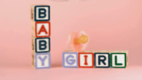 Baby shoes falling in front of baby blocks and soo Stock Video Footage