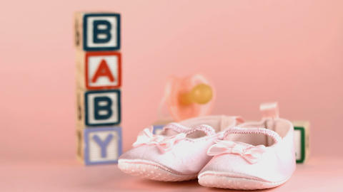 Baby shoes falling in front of baby blocks and soo Footage