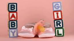 Pink soother falling onto baby shoes besides baby  Footage