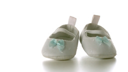 White baby shoes falling on white surface Footage