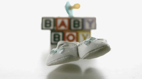Baby shoes falling in front of blue soother and ba Stock Video Footage