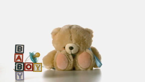 Teddy bear falling besides baby blocks and blue so Footage