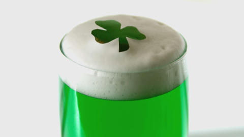 Shamrock confetti falling on pint of green beer 影片素材