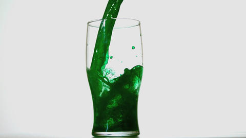 Green beer pouring into a pint glass on white back Stock Video Footage