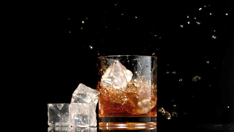 Ice cubes falling into glass of whiskey and ice Footage
