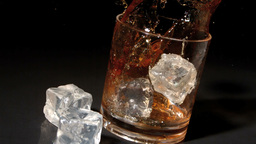 Ice cubes falling into tumbler of whiskey and ice Footage